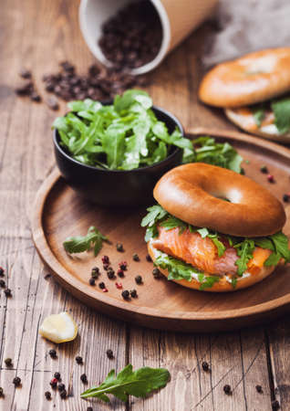 Sandwich with bagel and salmon, cream cheese and wild rocket in bowl and coffee cup with beans on wooden table background Zdjęcie Seryjne