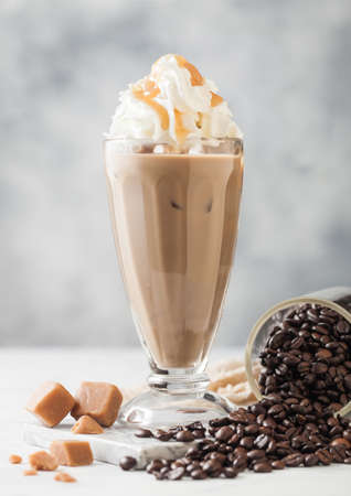 Black iced coffee with fresh milk and caramel with cream in classic milkshake glass and jar of raw coffee beans on light table background. Zdjęcie Seryjne