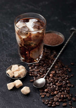 Black coffee with ice cubes and fresh milk with beans and cane sugar with ground coffee and long spoon on black background.