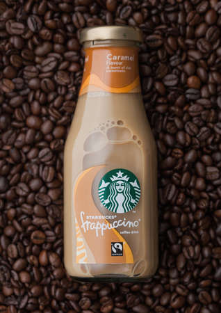 LONDON, UK - SEPTEMBER 09, 2020: Glass bottle of Starbucks frappuccino iced cold coffee on top of fresh raw coffee beans. Redakční