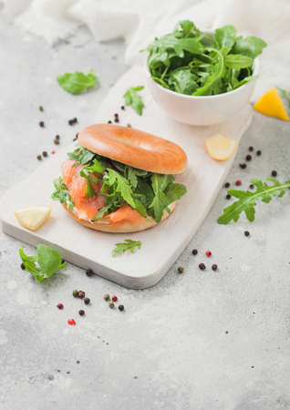 Bagel and salmon sandwich with cream cheese and wild rocket in white bowl and lemon with pepper. Zdjęcie Seryjne