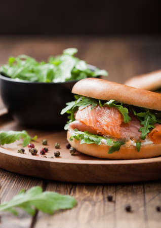Fresh healthy organic sandwich with salmon and bagel, cream cheese and wild rocket in plate on wooden background.