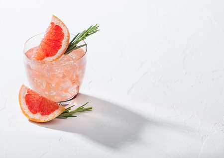 Refreshing summer red grapefruit cocktail in crystal glass with ice, fruit slice and rosemary on white background with deep shadow. Space for text