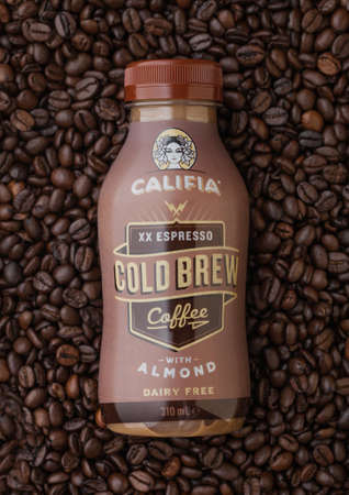 LONDON, UK - SEPTEMBER 09, 2020: Bottle of cold Califia espresso cold brew coffee with almonds on top of raw coffee beans.