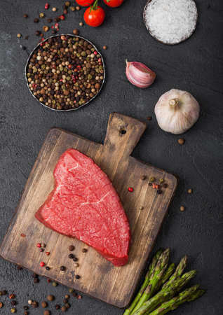 Slice of Raw Beef sirlion steak on wooden chopping board with tomatoes, garlic and asparagus tips on dark kitchen table background. Zdjęcie Seryjne