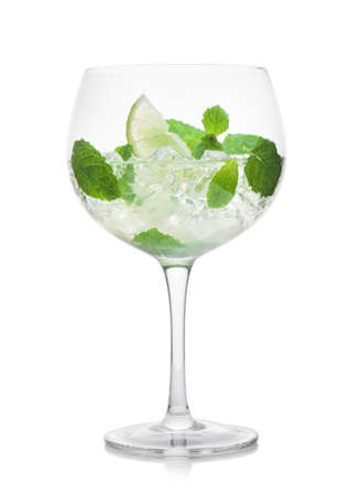 Glass of Mojito summer alcoholic cocktail with ice cubes mint and lime on white background.