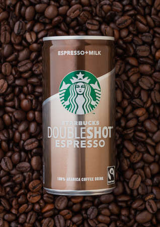 LONDON, UK - SEPTEMBER 09, 2020: Aluminum can of Starbucks doubleshot espresso cold coffee on top of fresh raw coffee beans.