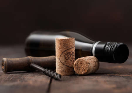 Wine corks with vintage corkscrew and bottle of white wine on wooden table background. Zdjęcie Seryjne