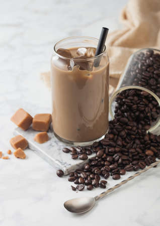 Iced cold coffee with milk and glass container of beans and spoon with salted caramel on marbel board and light table background.