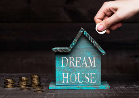 Wooden house model with coins next to it and hand holding the coin with conceptual text. Dream house Zdjęcie Seryjne