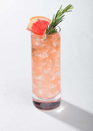 Highball glass of summer red grapefruit cocktail with ice cubes, fruit slice and rosemary on white background.