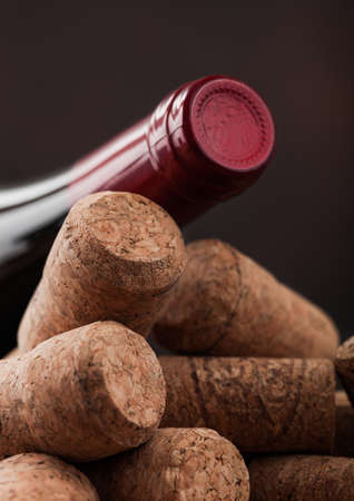 Bottle of red wine on top of various wine corks. Macro