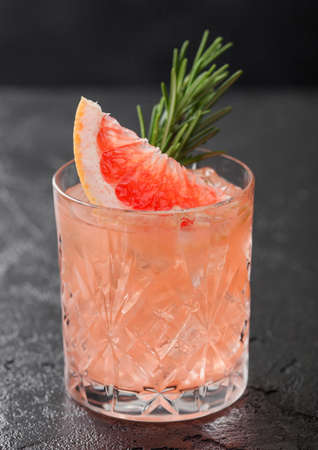 Grapefruit and rosemary drink, alcohol or non-alcohol cocktail in glass with ice cubes on black background. Macro