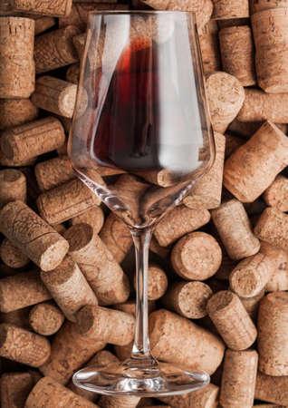 Luxury glass of red wine on top of various wine corks. Macro