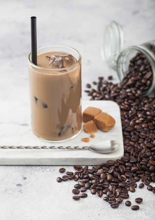 Glass of iced coffee with milk on marble board with jar of coffee beans and salted caramel and long spoon on light table background.