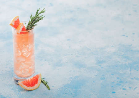Highball glass of refreshing summer red grapefruit cocktail with ice cubes, fruit slice and rosemary on blue background. Space for text Zdjęcie Seryjne