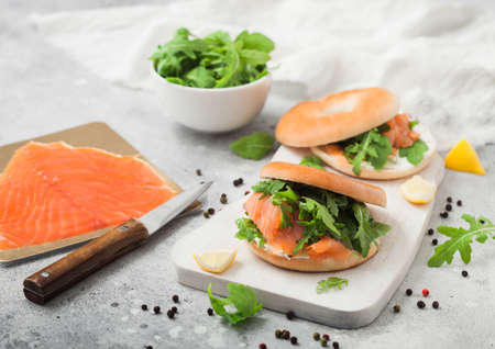 Fresh sandwiches with bagel and salmon, cream cheese and wild rocket on white board with smoked salmon pack and knife on light background.