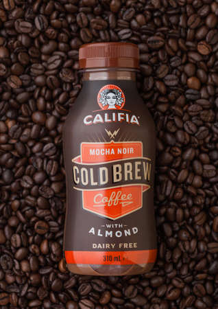 LONDON, UK - SEPTEMBER 09, 2020: Bottle of cold Califia mocha noir coffee with almonds on top of fresh raw coffee beans.