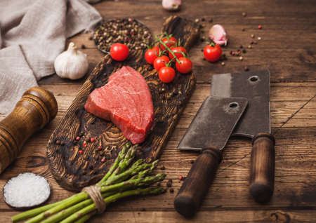 Slice of Raw Beef sirlion steak on wooden chopping board with tomatoes, garlic and asparagus tips and meat hatchets on wooden kitchen table background.