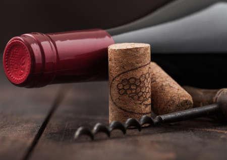 Wine cork with vintage corkscrew on wooden board background.