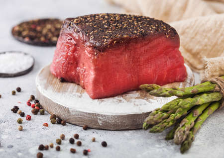 Slice of Raw Beef Topside Joint with Salt and Pepper on round chopping board with asparagus tips and garlic on light kitchen table background.