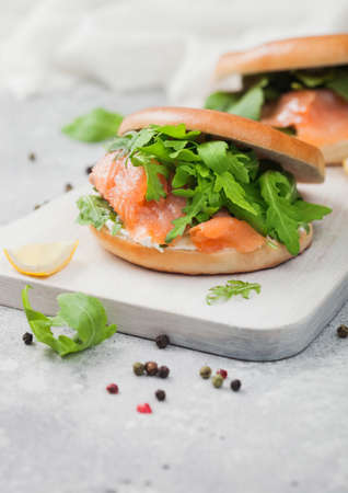 Organic healthy sandwiches with salmon and bagel, cream cheese and wild rocket and lemon and pepper on light. Zdjęcie Seryjne