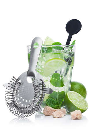 Luxury glass of Mojito summer alcoholic cocktail with ice cubes mint and lime on white background with cane sugar and raw lime with steel strainer
