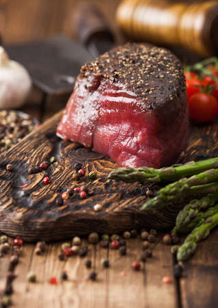Slice of Raw Beef Topside Joint with Salt and Pepper on wooden chopping board with tomatoes garlic and asparagus tips on wood kitchen table. Zdjęcie Seryjne