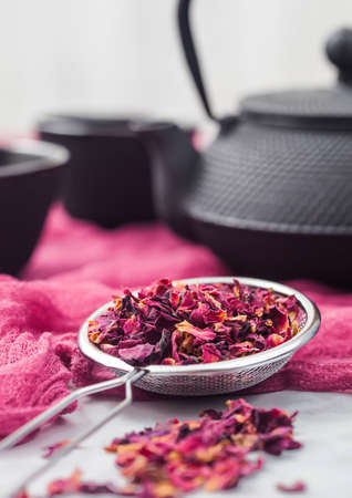 Strainer infusor with rose petals organic tea on red cloth background with iron teapot and cups. Foto de archivo