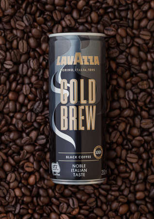 LONDON, UK - SEPTEMBER 09, 2020: Aluminium tin of Lavazza cold brew black coffee on on top of fresh raw coffee beans.
