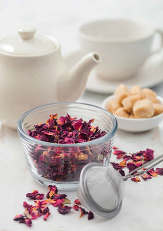 Fresh organic rose petals with strainer infuser and white ceramic teapot and cane sugar on white background.