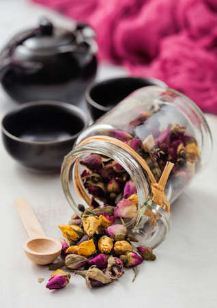 Glass jar of rose buds mix tea with wooden scoop on white background with black teapot and cups. Reklamní fotografie