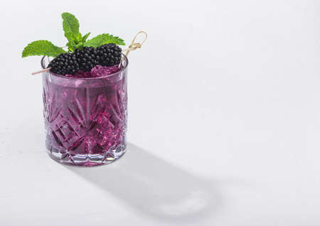 Glass of refreshing summer cocktail with blackberry, ice and mint on white background. Soda and alcohol mix. Hard light with deep shadow.