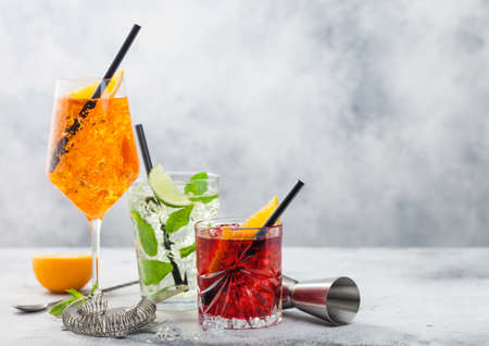 Glasses of spritz,mojito and negroni cocktails with ice cubes and lime and orange slices with mint leaf and black straw on light table background with strainer. Space for text