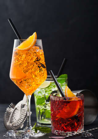 Glasses of spritz,mojito and negroni cocktails with ice cubes and lime and orange slices with mint leaf and black straw on dark background with strainer and spoon. Reklamní fotografie