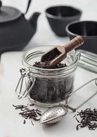 Black loose organic tea in glass jar with scoop and strainer infusor on light table background with iron teapot and cups.