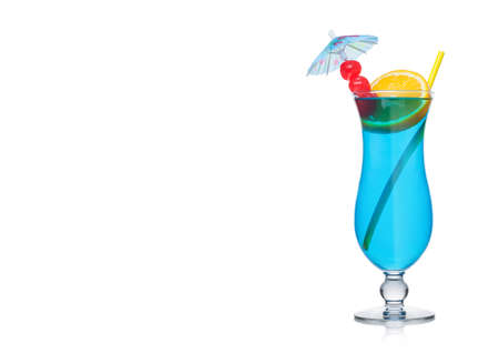 Blue cocktail classic glass with straw and orange slice with sweet cherry and umbrella on white background. Space for text