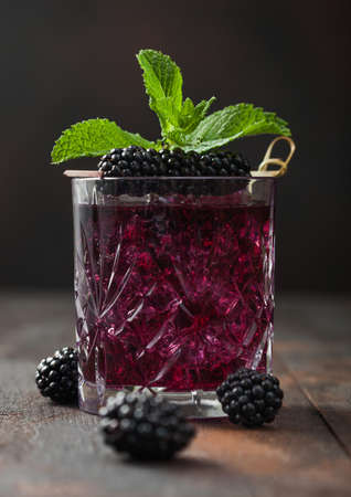 Glass of refreshing summer cocktail with blackberry, ice and mint on wooden background with raw berries. Soda and alcohol mix.