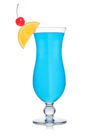 Blue cocktail classic glass with orange slice and sweet cherry on white background. Foto de archivo