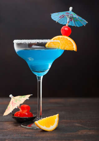 Blue summer cocktail in margarita glass with sweet cocktail cherries and orange slice with umbrella on dark table background. Reklamní fotografie