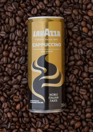 LONDON, UK - SEPTEMBER 09, 2020: Aluminium tin of Lavazza cappuccino iced cold coffee on top of fresh raw coffee beans.