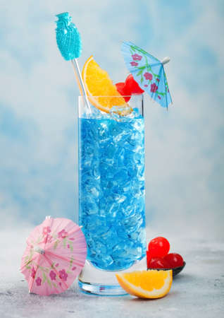 Blue summer cocktail in highball glass with sweet cocktail cherries and orange slice with umbrella on blue table background.