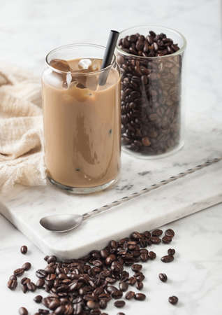 Iced cold caramel coffee with milk and glass container of beans and spoon on marbel board and light table background.