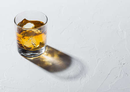 Glass with ice cubes of single malt whiskey on white background with deep shadow.