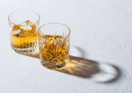 Glasses with ice cubes of single malt whiskey on white background with deep shadow.