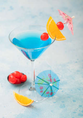 lagoon summer cocktail in martini glass with sweet cocktail cherries and orange slice with umbrella on blue table background.