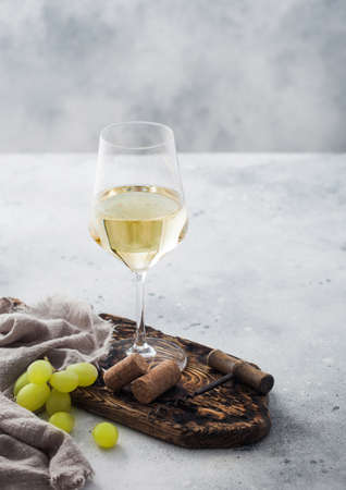 Glass of white homemade wine with corks, corkscrew and grapes on wooden board with linen cloth on light table background.