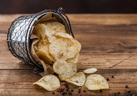 Potato crisps chips with black pepper in steel snack bucket on wooden table background.