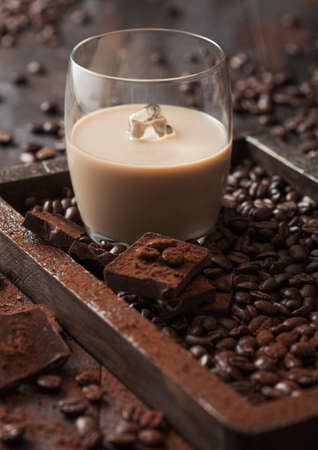Glass with ice cubes of Irish cream baileys liqueur in wooden tray with coffee beans and powder with dark chocolate on dark wood background. Top view