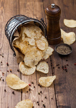 Potato crisps chips crunchy snack with black pepper in steel bucket on wooden table background with mill and ground pepper. Reklamní fotografie